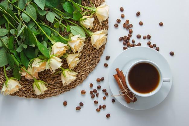 Vue de dessus une tasse de café avec des fleurs sur un dessous de plat sur une surface blanche. horizontal
