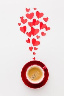 Vue de dessus d'une tasse de café avec des formes de coeur en papier de la saint-valentin