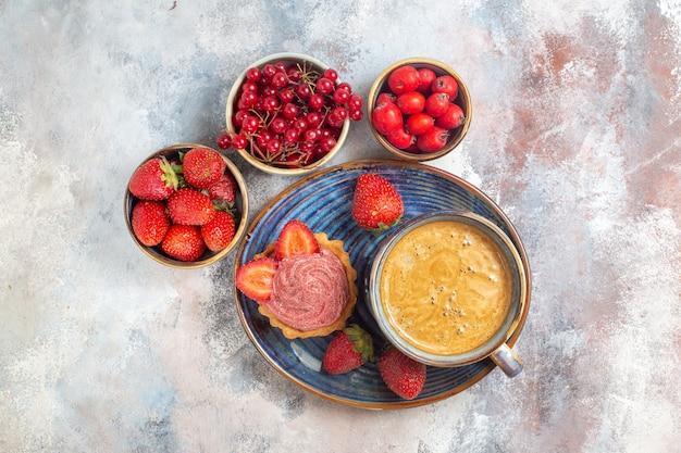 Vue de dessus tasse de café avec gâteau et fruits rouges sur table lumineuse gâteau biscuit sucré