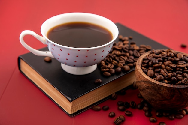 Vue de dessus d'une tasse de café avec des grains de café isolé sur fond rouge