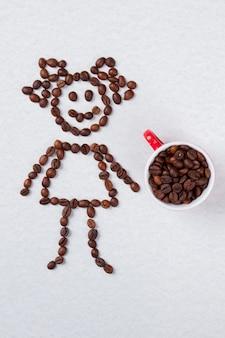 Vue de dessus tasse de café avec des grains crus. fille symbolique faite de grains de café sur une surface isolée blanche.