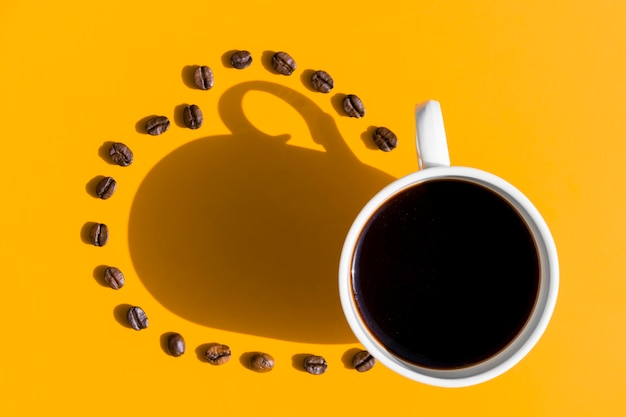 Vue de dessus tasse de café avec des grains