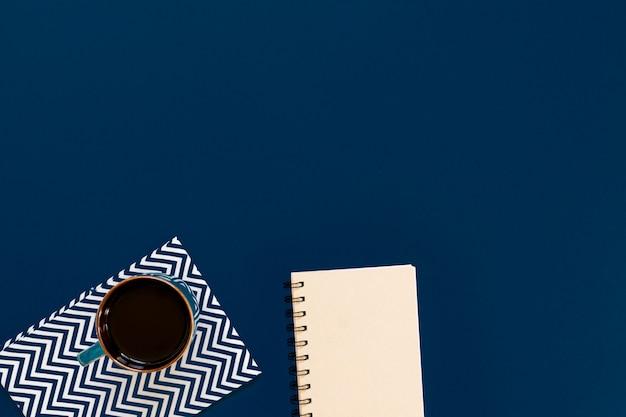 Vue de dessus de tasse de café noir et cahier propre sur fond bleu avec espace de copie.