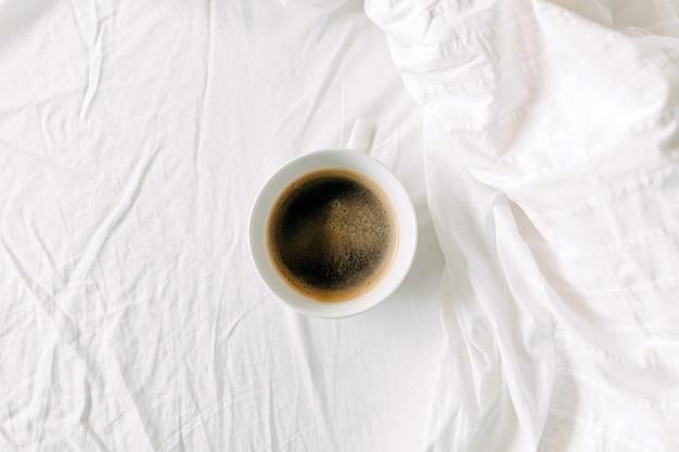 Vue de dessus d'une tasse de café noir sur un drap blanc petit-déjeuner au lit concept