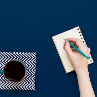 Vue de dessus de tasse de café noir et femme main écrit dans le cahier sur fond bleu avec copie espace.