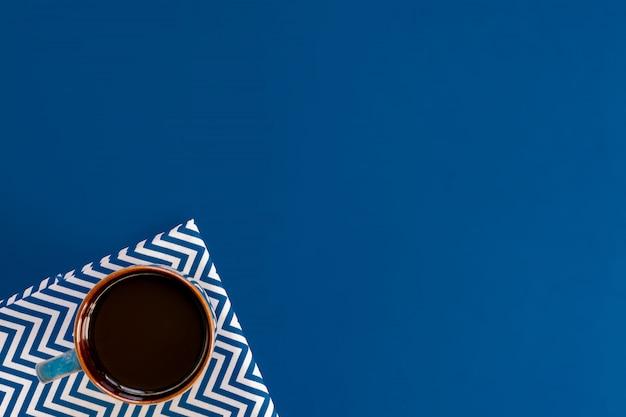 Vue de dessus de la tasse de café noir sur fond bleu avec espace de copie.