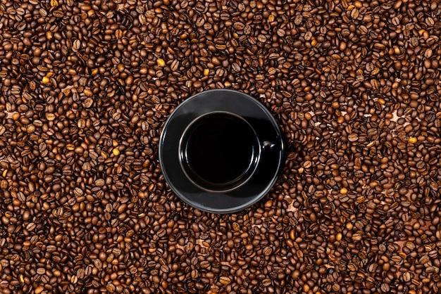 Vue de dessus de la tasse de café noir sur le fond des grains de café