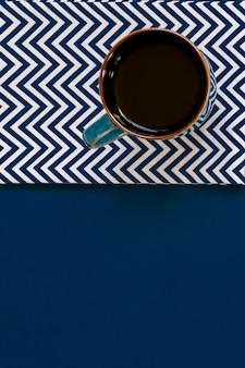 Vue de dessus de tasse de café noir sur une serviette textile sur fond bleu avec copie espace.