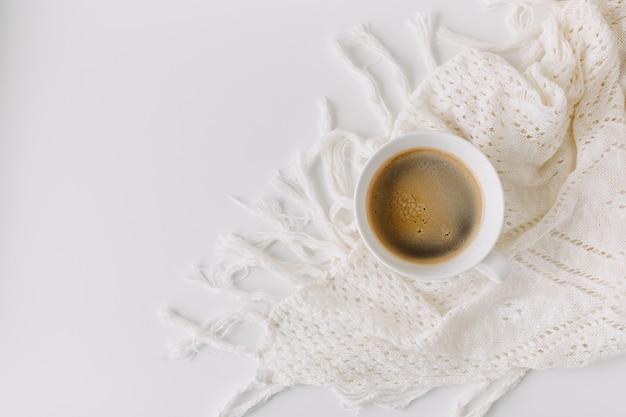 Vue de dessus sur une tasse de café noir sur table blanche avec une couverture au crochet