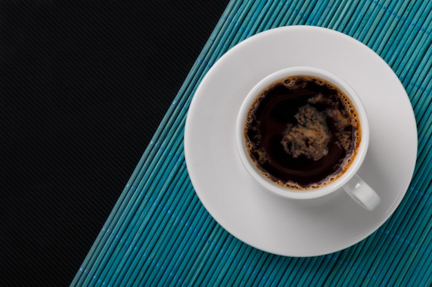 Vue de dessus d'une tasse de café noir sur un tapis en bambou bleu et fond texturé noir