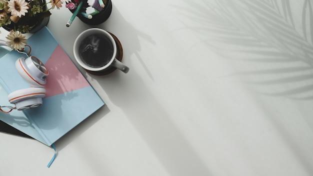 Vue de dessus de la tasse de café, ordinateur portable, casque sur table blanche