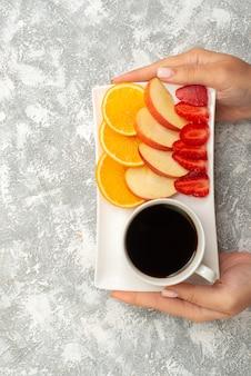 Vue de dessus tasse de café avec des pommes tranchées oranges et fraises sur fond blanc fruits mûrs frais mellowtop