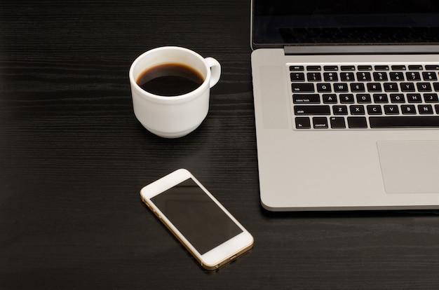 Vue de dessus de la tasse à café, smartphone et clavier d'ordinateur portable, tableau noir