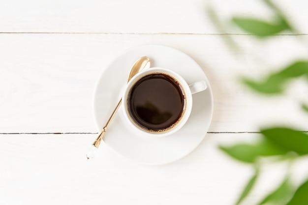Vue de dessus d'une tasse de café sur une table en bois blanche et des feuilles vertes.