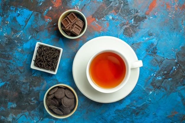 Vue de dessus une tasse de chocolats au thé dans de petits bols sur une surface bleu rouge