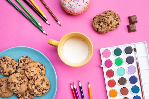Vue de dessus de la tasse avec du lait et des biscuits colorés, accompagnés de crayons et aquarelles sur un backgrou rose