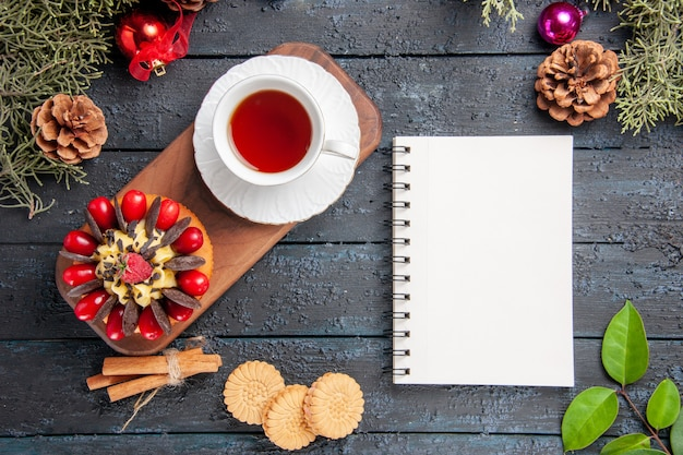 Vue de dessus une tasse de gâteau de thé et de baies sur une assiette en bois de pommes de pin jouets de noël feuilles et un cahier sur une table en bois sombre