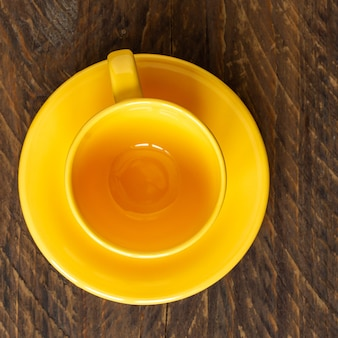 Vue de dessus de la tasse jaune vide et soucoupe sur fond rustique en bois. vaisselle de cuisine.