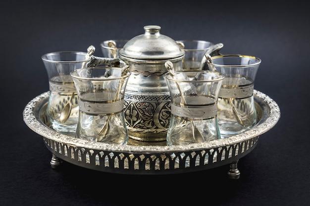 Vue de dessus d'une tasse métallique et de verres en cristal turc sur un plateau circulaire métallique