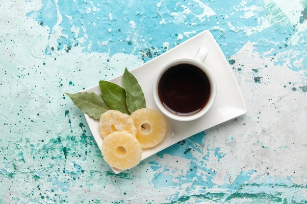 Vue de dessus tasse de thé avec des anneaux d'ananas séchés sur une surface bleu clair