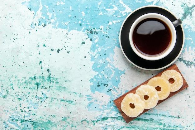 Vue de dessus tasse de thé avec des anneaux d'ananas séchés sur la surface bleue
