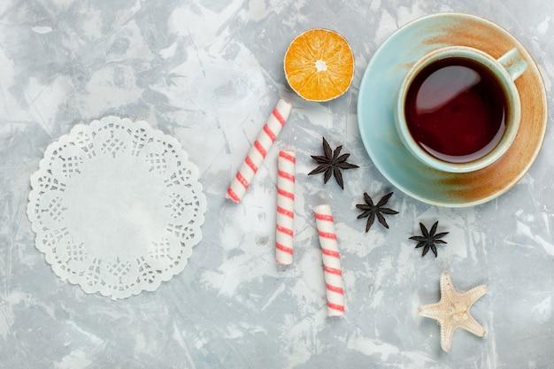 Vue de dessus tasse de thé au citron et bonbons sur fond blanc clair bonbons fruits thé sucré