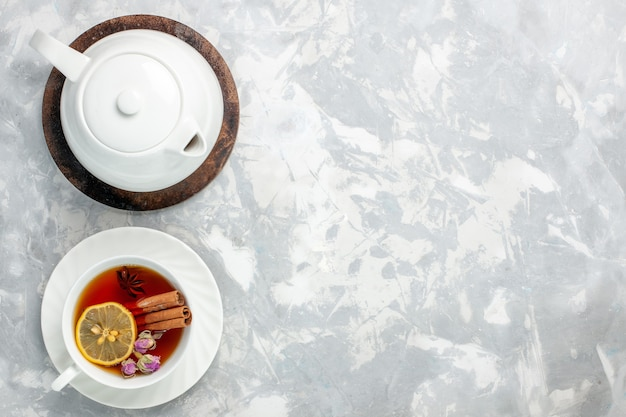 Vue de dessus tasse de thé au citron et à la cannelle sur la surface blanche claire