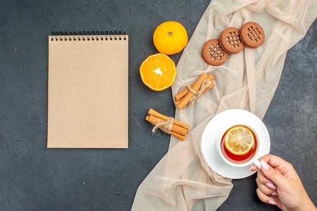 Vue de dessus une tasse de thé au citron dans la main féminine bâtons de cannelle cookies sur bloc-notes orange châle beige sur surface sombre