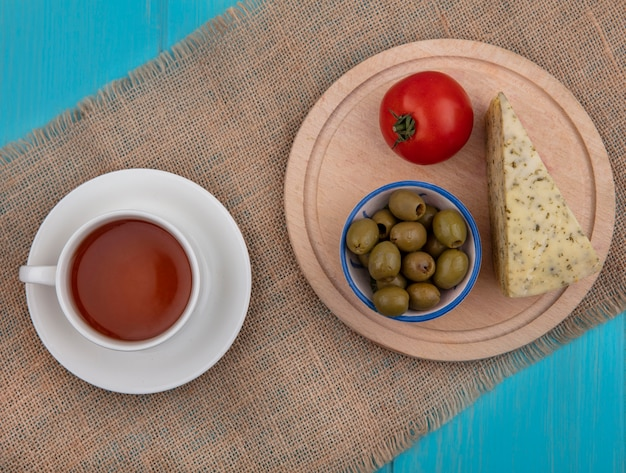 Vue de dessus tasse de thé aux olives au fromage et tomate sur un support sur une serviette beige