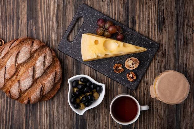 Vue de dessus tasse de thé aux olives dans une soucoupe avec du fromage maasdam sur un support avec du yogourt et du pain noir sur un fond en bois