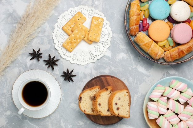 Vue de dessus tasse de thé avec des bagels de gâteau et des macarons sur blanc