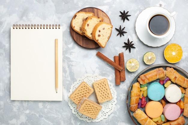 Vue de dessus tasse de thé avec des bagels et des macarons sur blanc