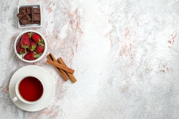 Vue de dessus de la tasse de thé avec des baies de cannelle sur une surface blanche