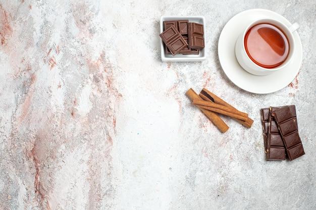 Vue de dessus de la tasse de thé avec des barres de chocolat sur une surface blanche