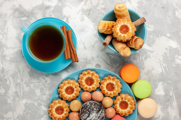 Vue de dessus tasse de thé avec biscuits bagels et macarons sur la surface blanche