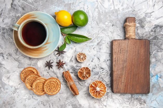 Vue de dessus tasse de thé avec biscuits et citron sur la table lumineuse biscuit thé fruit