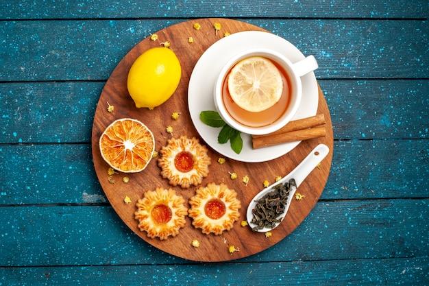 Vue de dessus tasse de thé avec des biscuits et du citron sur le bureau bleu