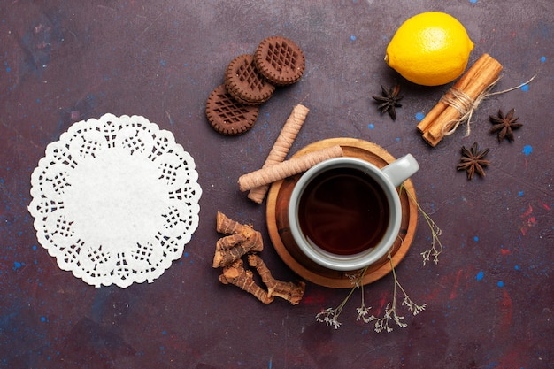 Vue de dessus tasse de thé avec des biscuits et du citron sur fond sombre thé couleur douce photo