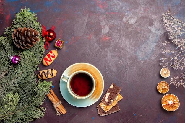 Vue de dessus tasse de thé avec des biscuits sur l'espace sombre