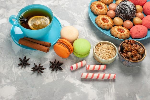 Vue de dessus tasse de thé avec des biscuits et des gâteaux macarons français sur la surface blanche
