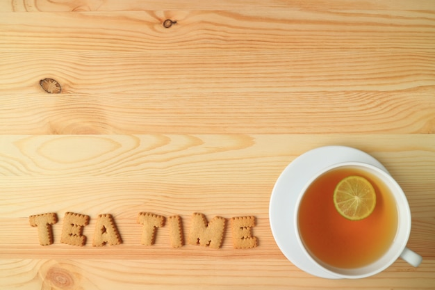 Vue de dessus d'une tasse de thé et de biscuits à la lime chaude orthographe du mot heure du thé sur table en bois