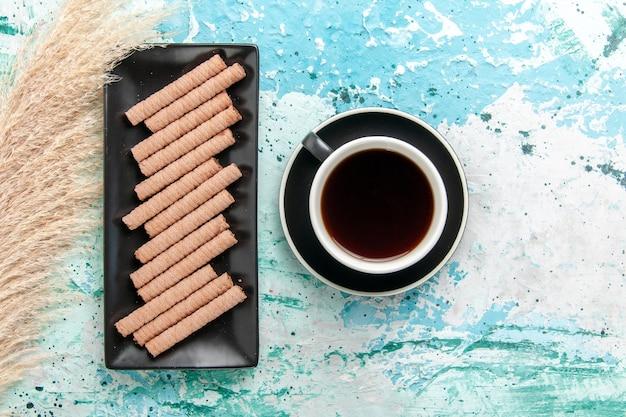 Vue de dessus tasse de thé avec des biscuits sur la surface bleue