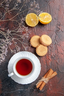 Vue de dessus tasse de thé avec des biscuits sur la table sombre sucre thé photo biscuit sucré