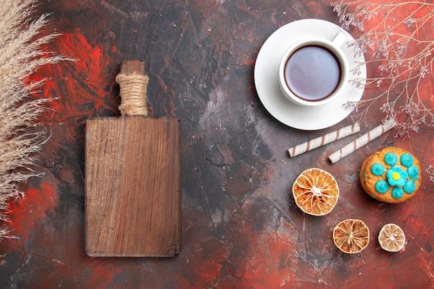 Vue de dessus tasse de thé avec des biscuits sur table sombre