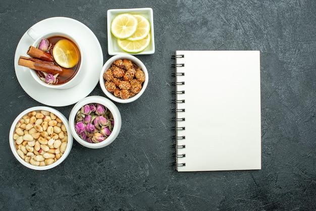 Vue de dessus tasse de thé avec bloc-notes aux noix et bonbons sur surface sombre cérémonie du thé bonbons aux noix
