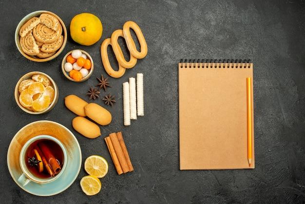 Vue de dessus tasse de thé avec des bonbons biscuits et fruits sur table grise thé biscuits sucrés