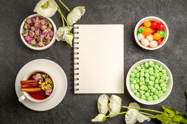 Vue de dessus tasse de thé avec des bonbons sur le bureau gris saveur arc-en-ciel de couleur de thé