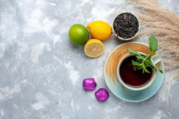 Vue de dessus tasse de thé avec des bonbons de citrons frais et du thé séché sur la table lumineuse, thé aux agrumes de fruits