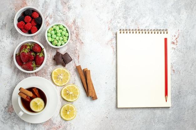 Vue de dessus de la tasse de thé avec des bonbons et des fraises sur une surface blanche