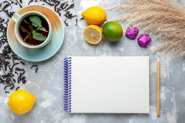 Vue de dessus tasse de thé avec des bonbons de grains de thé séchés frais et de citron sur la table lumineuse, petit déjeuner de thé